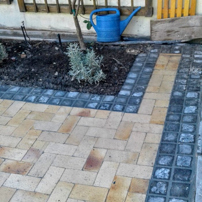 CEMENT COBBLES DOUBLE CHARCOAL BORDER AROUND CLAY PAVERS