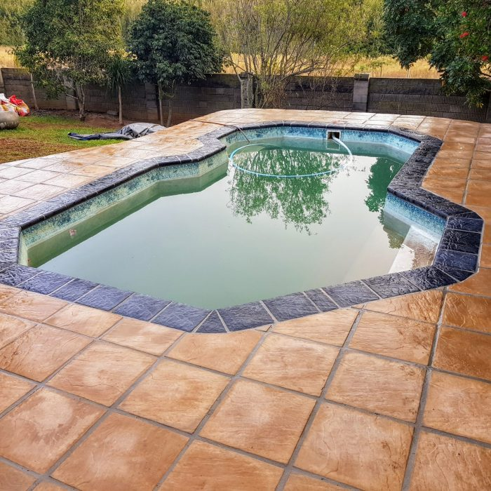 SEALED SANDSTONE SLABS WITH CHARCOAL COPING AROUND POOL
