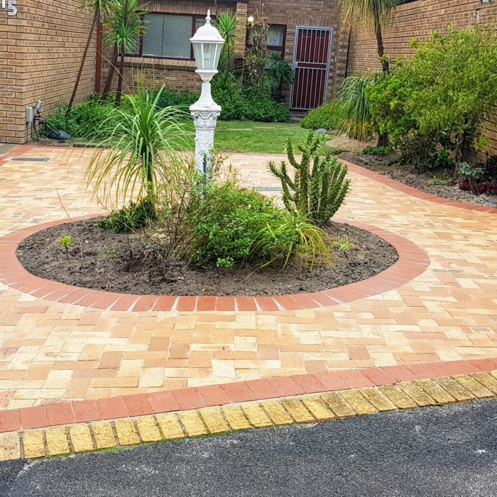 WHEATSTONE PAVERS AROUND A FOUNTAIN WITH A RED DE HOOP BORDER
